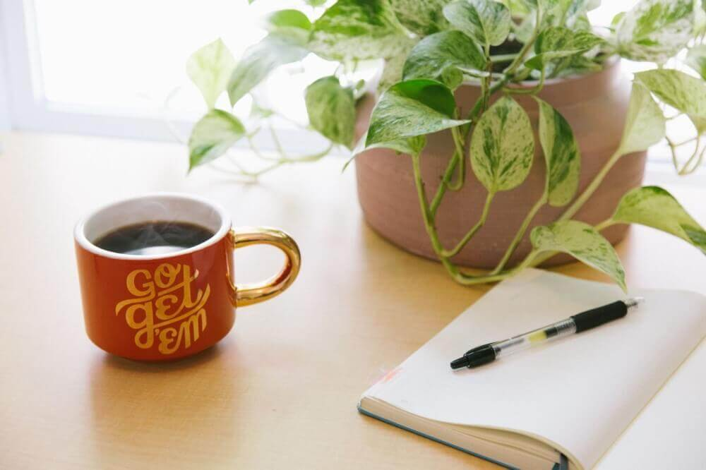 a notebook and pen next to a mug of black coffee